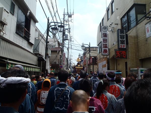 蒲田温泉の横を神輿が通る
